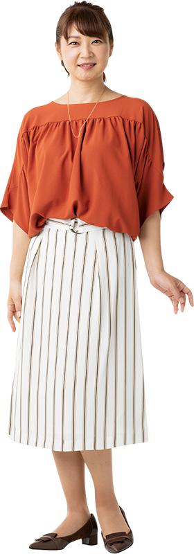 レンガ色のプルオーバーに白に黒の細いストライプが入ったスカートをはいた女性