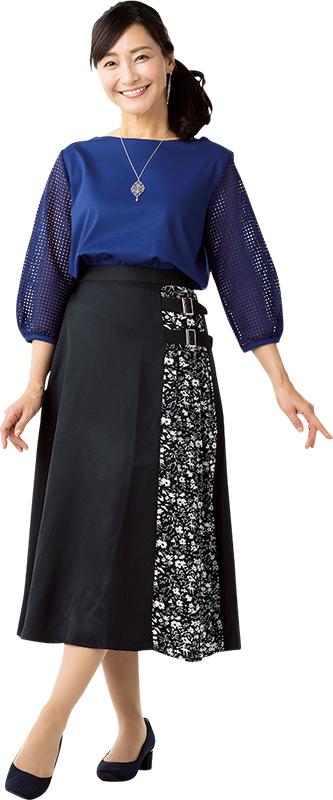 ロイヤルブルーのトップスに黒地のスカートにベルトと花柄の切り替えが入ったものを合わせている女性