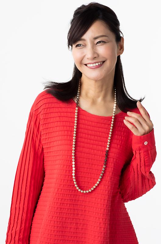 赤いプルオーバーにロングネックレスを合わせた女性