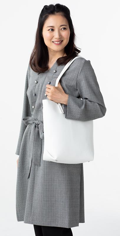 グレーのワンピースに白い肩掛けバッグを持っている女性