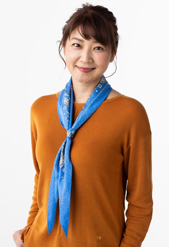 キャメルカラーのトップスに鮮やかなブルーのスカーフをV字につけた女性