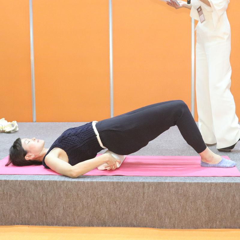 枕を腰の下に入れる女性と杉浦由里子さん