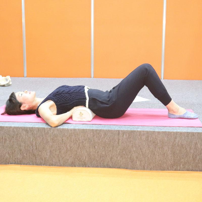 枕を腰の下に置き、膝を曲げて仰向けで寝る