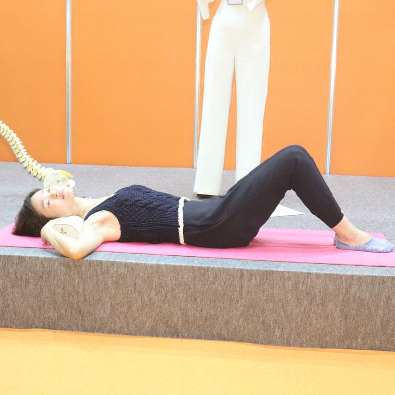 枕を首の下に置き、膝を立てて仰向きになる。首を左右に動かす女性