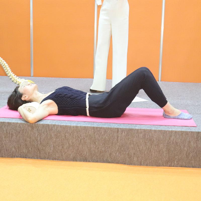 首の下に枕を入れ、仰向けになって寝る女性