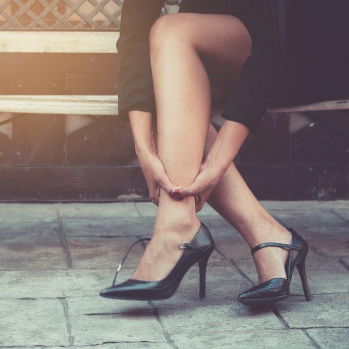 足首を押さえる、ヒールを履いた女性