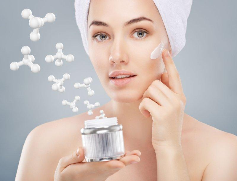 クリームを頬に塗る女性の写真