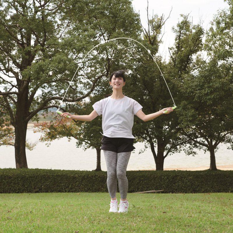 タニタの『タニタサイズ カロリージャンプ TS-960』を使って外で縄跳びする女性