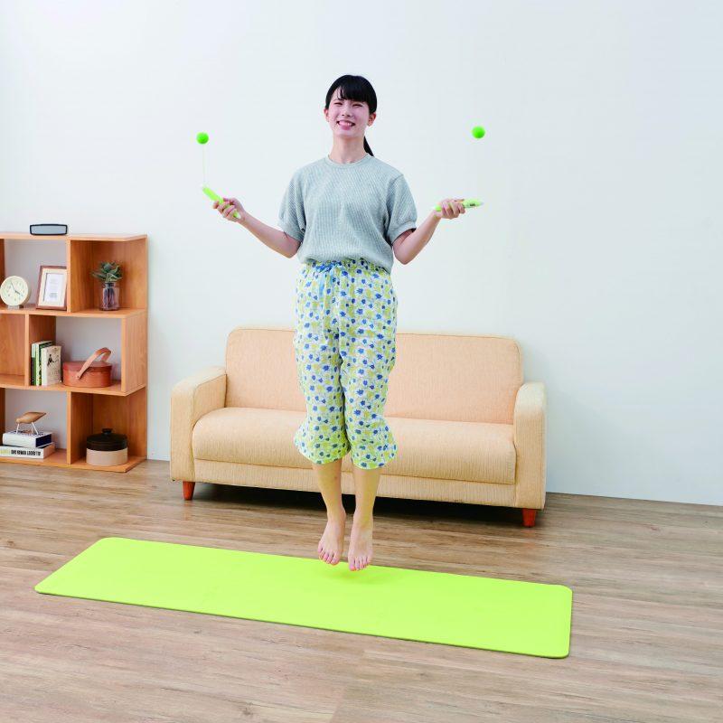 タニタの『タニタサイズ カロリージャンプ TS-960』を使って部屋で縄跳びをする女性