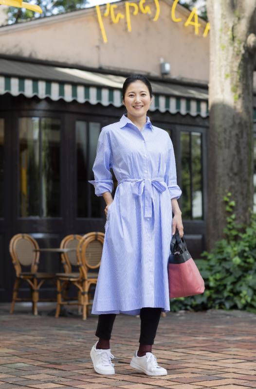 ブルーの縦ストライプのシャツワンピースを着た女性