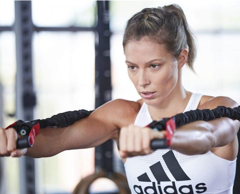 アディダスのパワーチューブを使ってトレーニングしている女性