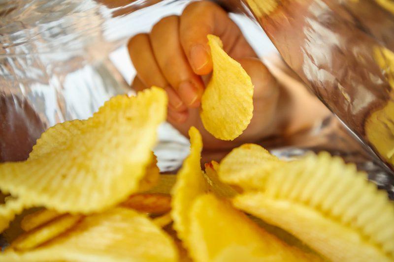 袋に入ったポテトチップスに手を伸ばしている