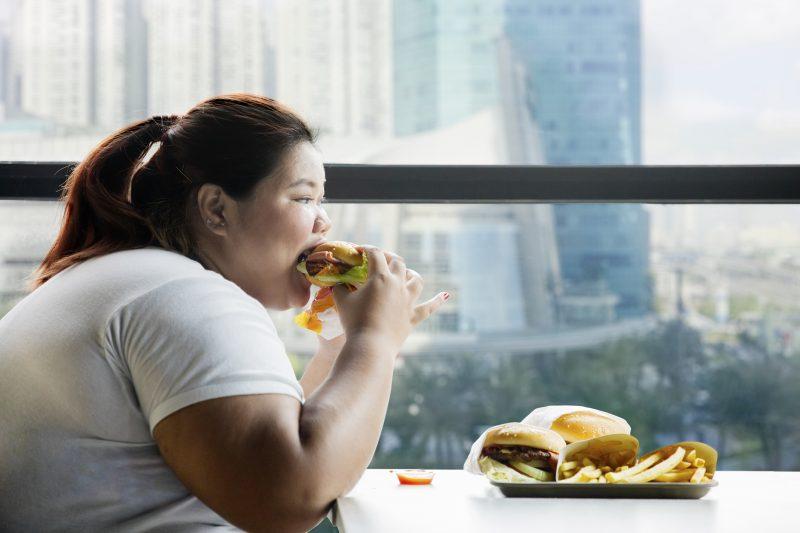 太った女性がハンバーガーにかぶりついている