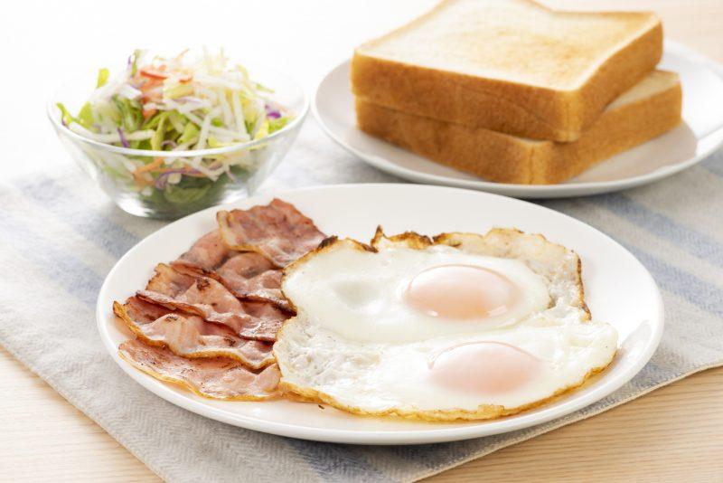 目玉焼きにベーコン、食パンとサラダがテーブルに用意されている