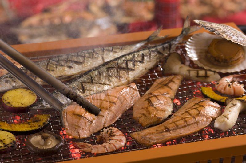 鮭やさんまが網で焼かれている