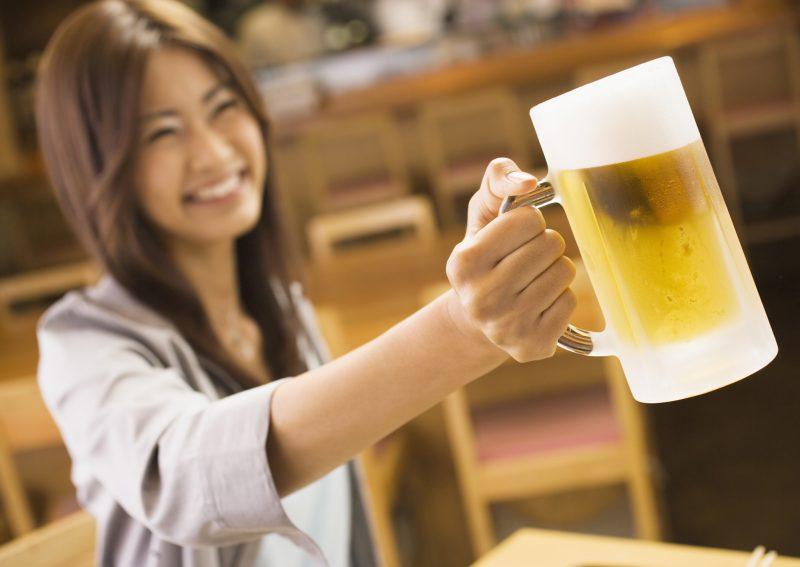 ビールグラスを手に笑顔の女性