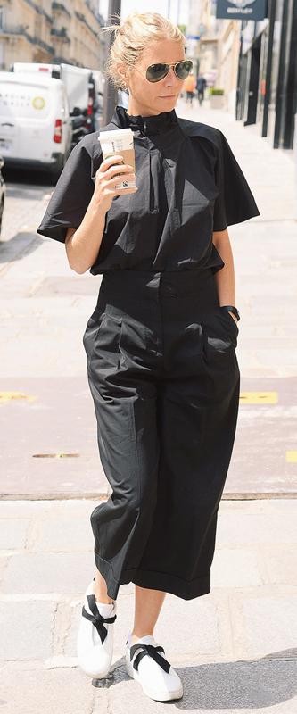 グウィネス・パルトローが黒いトップスとスカートに、黒のリボンが付いた白いスニーカーを履いている
