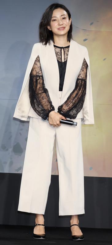 黒のレースブラウスに白のケープ風のトップス、パンツを合わせた菅野美穂
