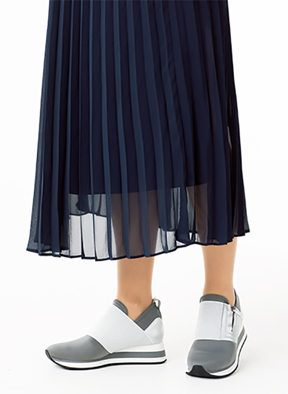 プリーツスカートをはいた女性の脚元