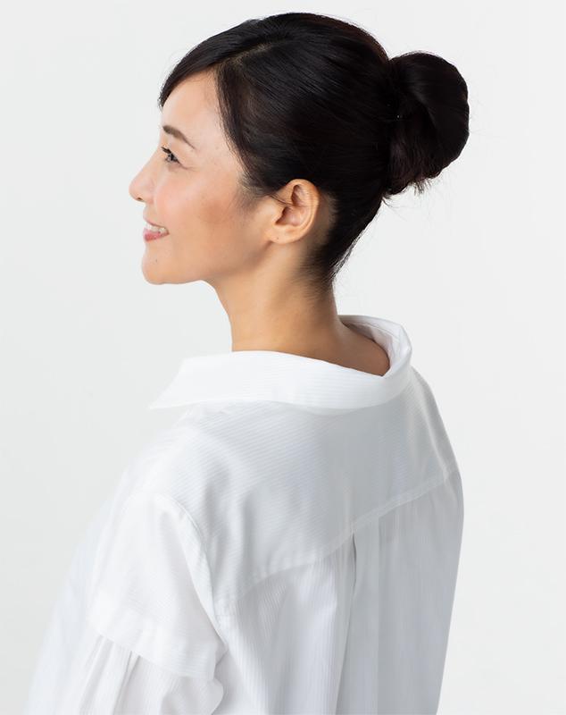 女性が白いブラウスを抜き襟して着ている