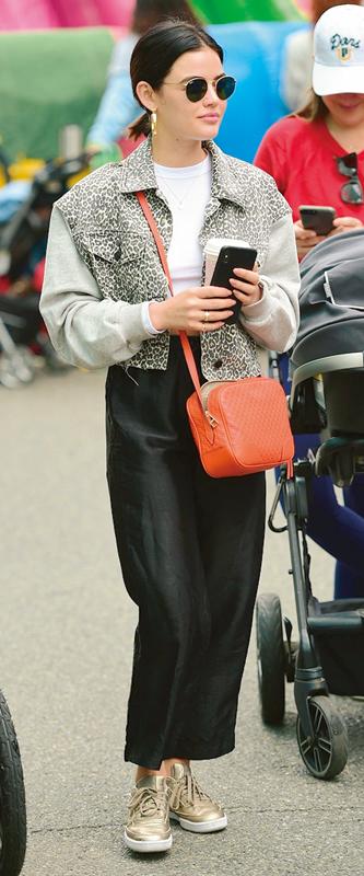 ルーシー・ヘイルが白いTシャツにレオパード柄のブルゾン、黒のロングタイトスカートに金色のスニーカーを履いている