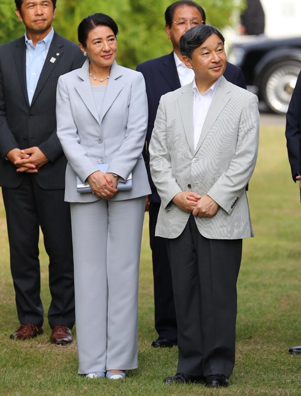 天皇陛下に寄り添われる、グレーがかった薄いブルーのパンツスーツの雅子さま