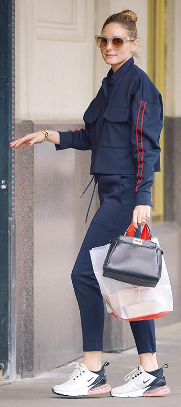 オリヴィア・パレルモがスポーティなネイビーのセットアップに黒のミニバッグ、ハイテクスニーカーを履いている