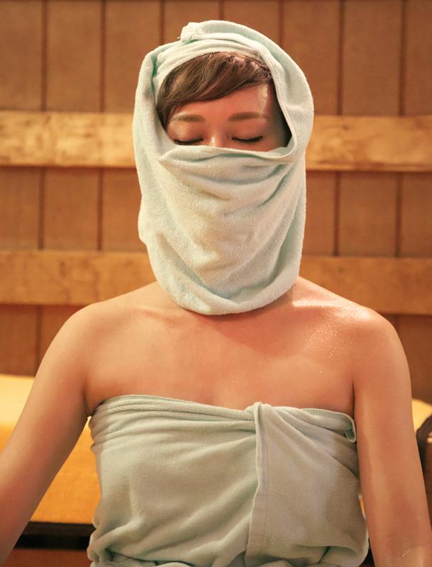 サウナでタオルを顔に巻いた女性の写真