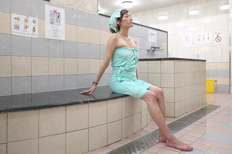 公共の風呂場で腰掛け、目をつぶって休憩する女性の写真