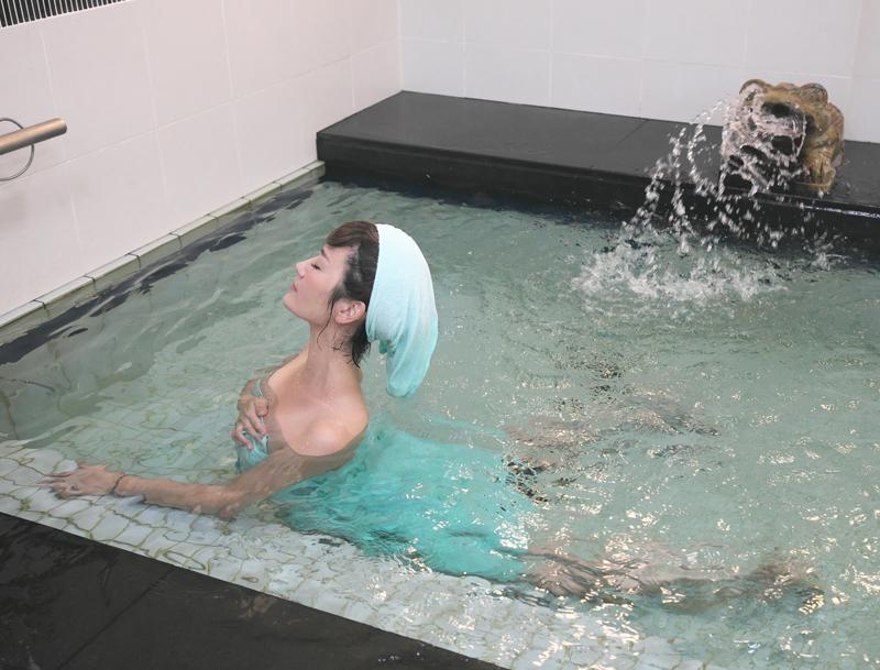 お風呂の中で上半身を反らす女性の写真