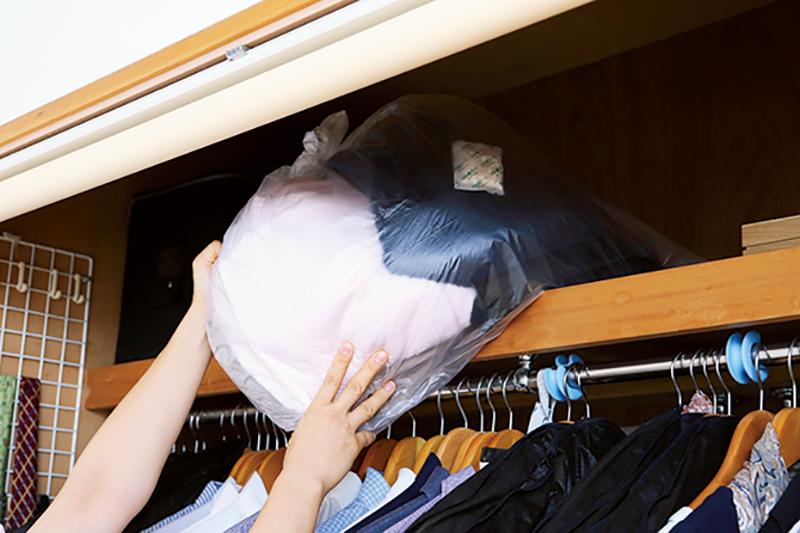 天袋にビニール袋に入れた衣類を収納する写真