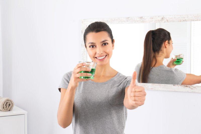 マウスウォッシュのグラスを手に親指を立ててポーズをとる女性の写真