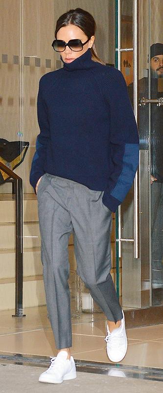 ヴィクトリア・ベッカムがネイビーのセーターにグレーのパンツ、白いスニーカーを履いている