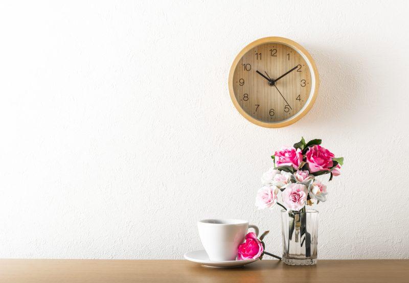 木目調のダイニングテーブルにバラの入った花瓶とコーヒーカップが並んでいる