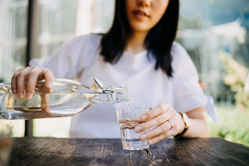 ボトルから水をグラスに注ぐ女性