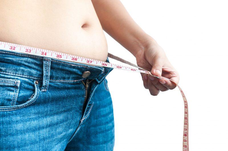 お腹に脂肪のついた女性がメジャーでウエストを測っている