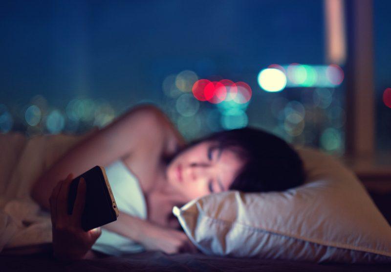 夜中スマートフォンを見つめている女性