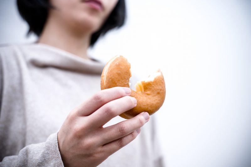 ドーナツを手にストレスに満ちた顔をする女性