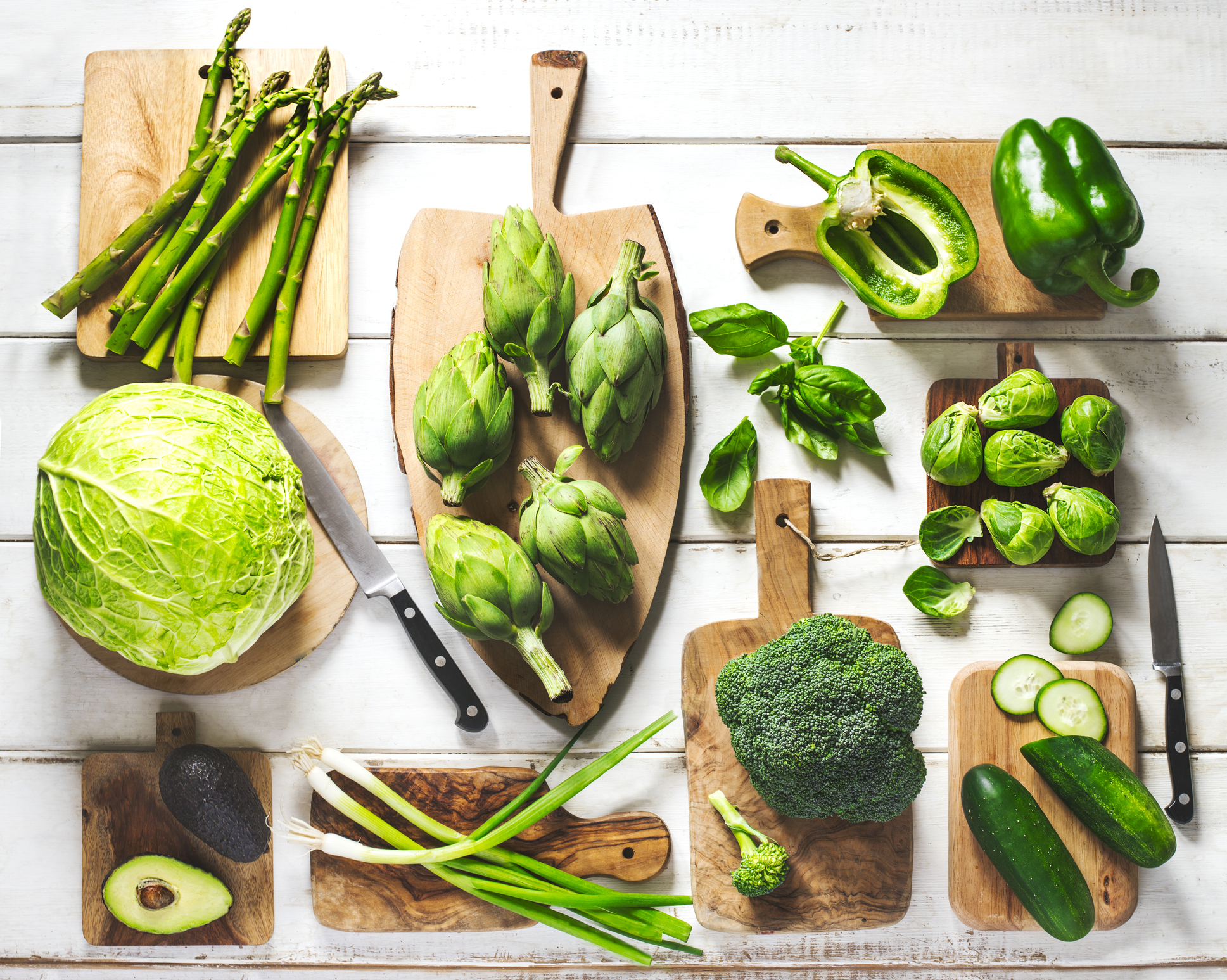 カッティングボードにアスパラガスやブロッコリー、キャベツなど緑色の野菜がのっている