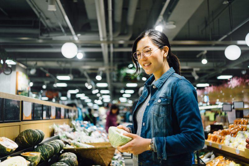 スーパーでキャベツを手に笑顔で悩む女性