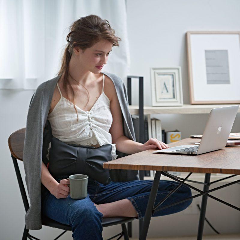 ルルド シェイプアップベルトを装着してダイニングテーブルの椅子に腰かけてくつろぐ女性