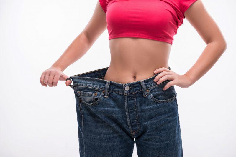 ウエストの細い女性が大きいサイズのジーンズをはいて痩せたことをアピールしている