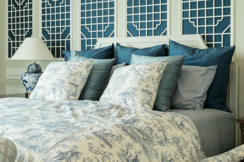 青いカバーのかかった寝具がセットされているベッドルーム