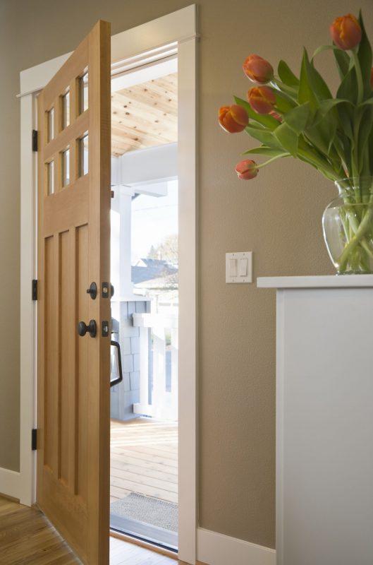玄関にあるシューズボックスにオレンジ系のチューリップが入った花瓶が置かれている