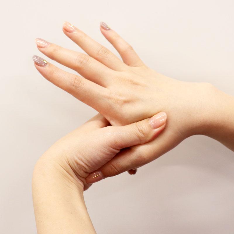 ハンドクリームを親指と人差指の間に塗っている様子