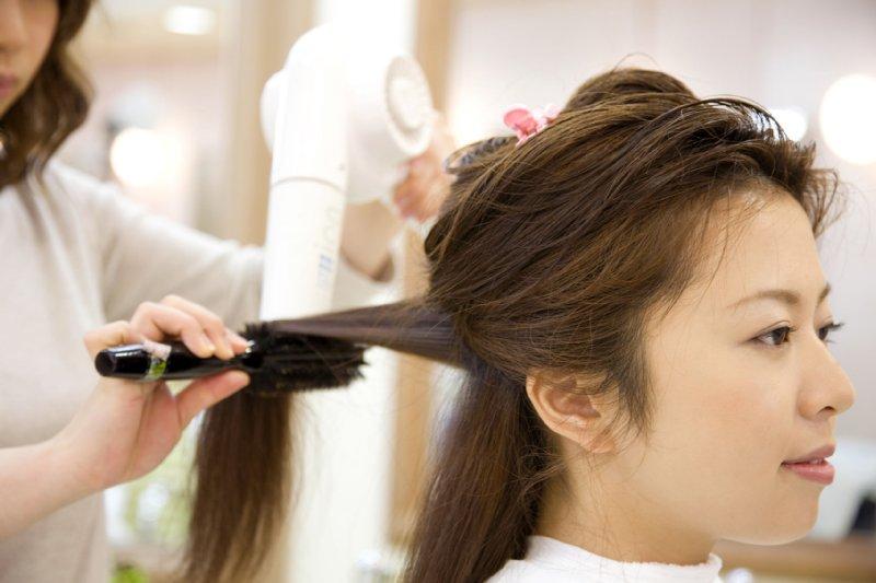 美容院で髪を整えてもらう女性