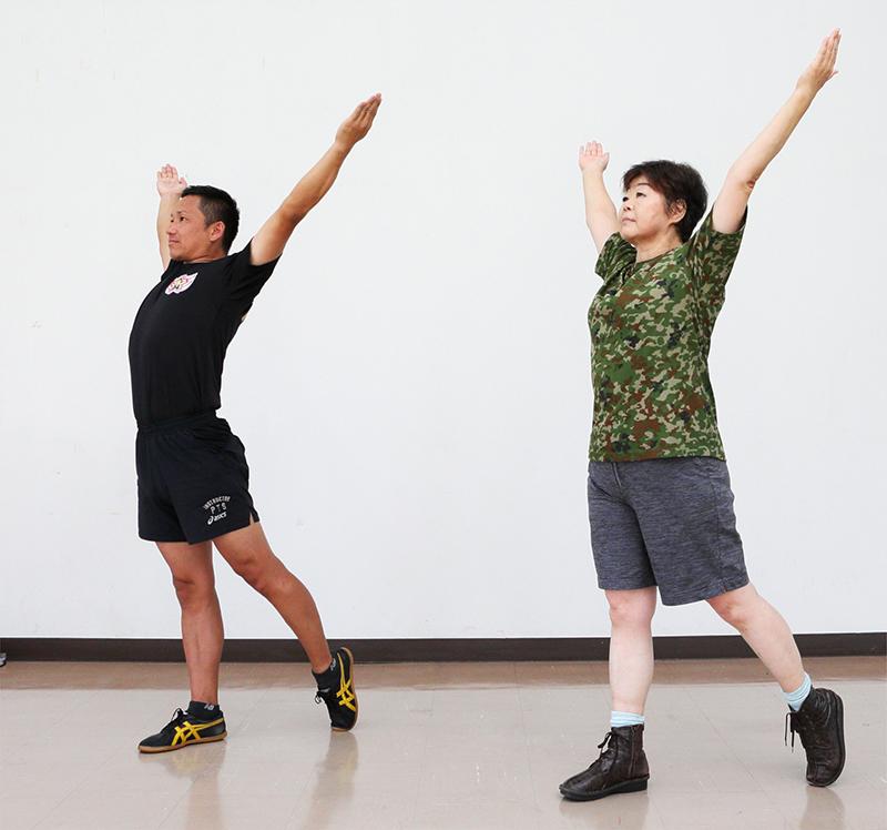 右脚を一歩前に出して体重を乗せ両手を挙げて胸を開く運動をするオバ記者