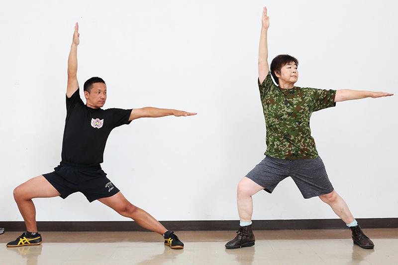 右ひざを曲げて、左脚は横にまっすぐ伸ばす。左手を横に、右手を上に挙げるオバ記者