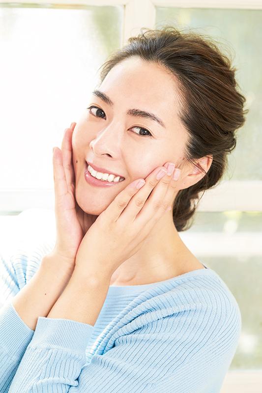 笑顔で頬に手を当てている美しい肌の女性