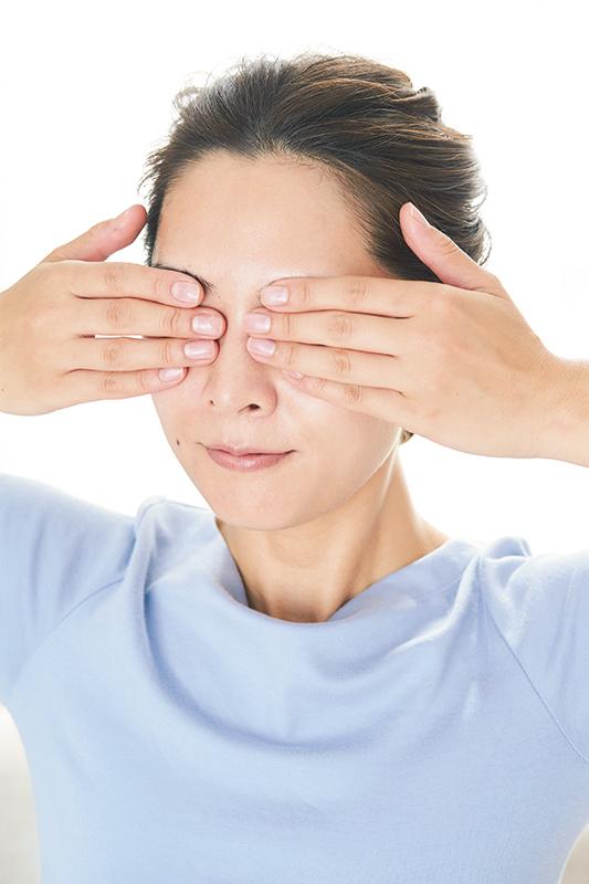 手のひらで目を包み込むようにしてジェルを塗っている女性